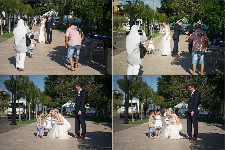 candid moment with the bride and groom on the sidewalk next to lake garda