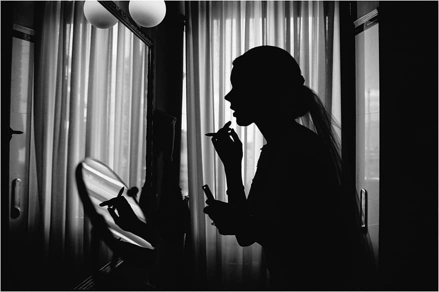 silhouette of a bride putting her make up on