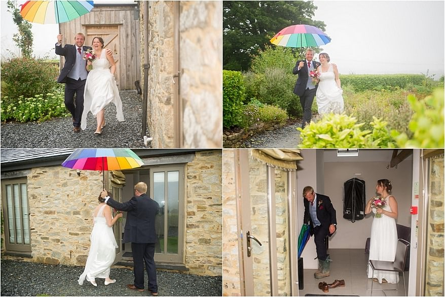 bride and groom holding a umbrella and wearing wellies due to the rain