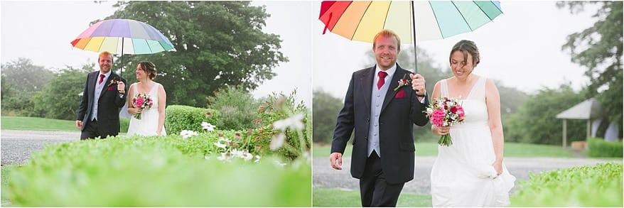 groom holding an umbrella over the bride to keep her dry from the rain