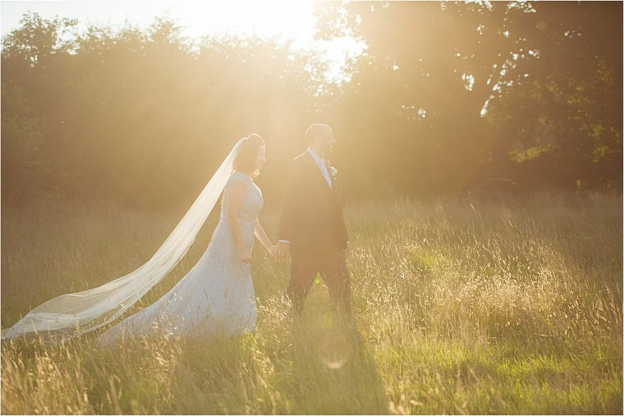 sun flair with the bride and groom walking at trevenna barns