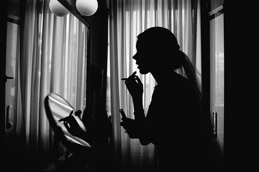 A black and white photograph of a bride applying make up.