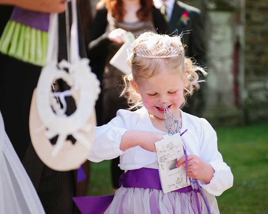 Flowergirl outside a church poking herself in the nose
