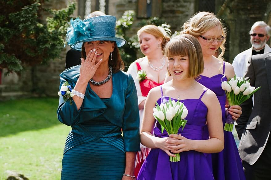 Emotional mum looking at her daughter getting out of a VW campervan outside the a church in Truro