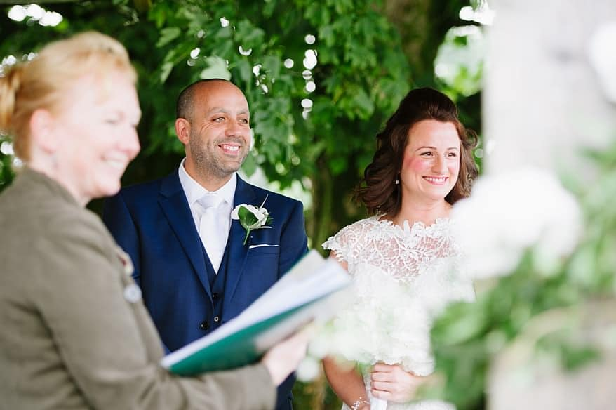 Bride and groom smiling at their wedding guest at Trevenna Barns