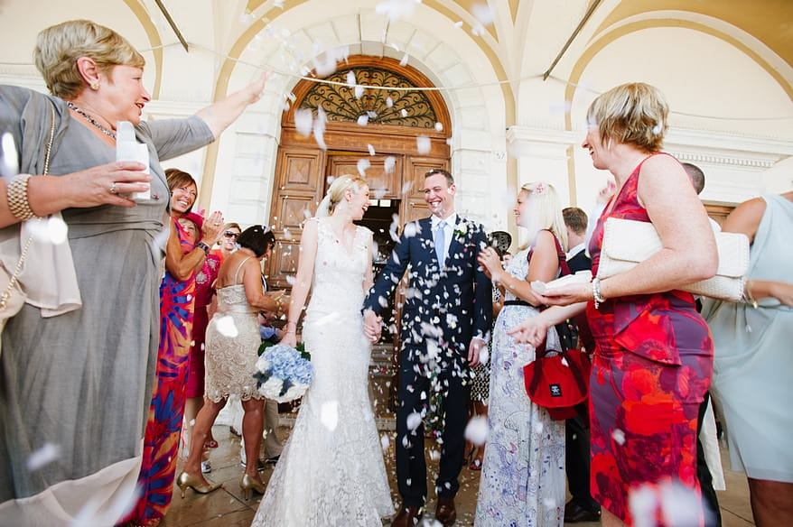 Happy Bride and groom walking under loads of confetti in Lake Garda