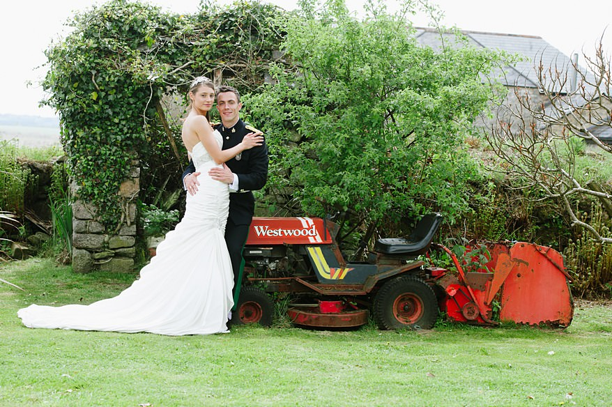 Bride and groom at on the red tractor at Trevenna Barns