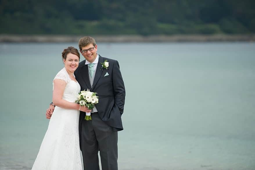Bride and groom in love on the beach in falmouth over looking pendennis castle