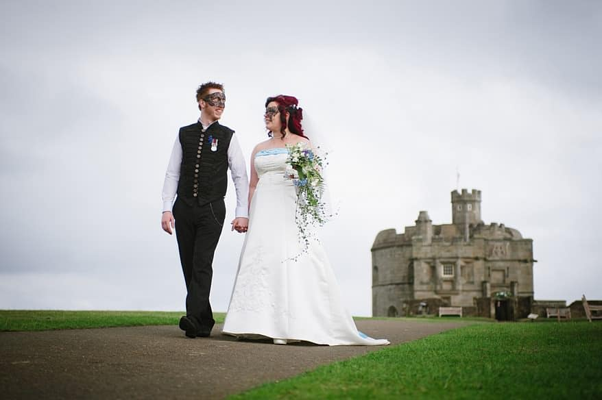 bride and groom walking hand in hand with pendennis castle in the background