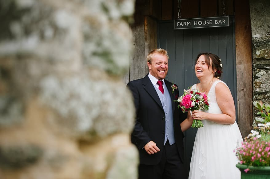 happy wedding couple in the doorway of a barn at Trevenna Barns