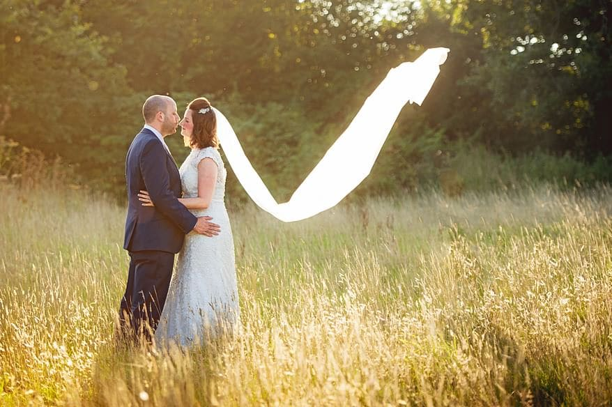 Bride with a flowing vail in the long grass at Trevenna Barns