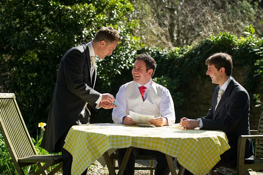 Grooms men in the garden looking at the wedding rings