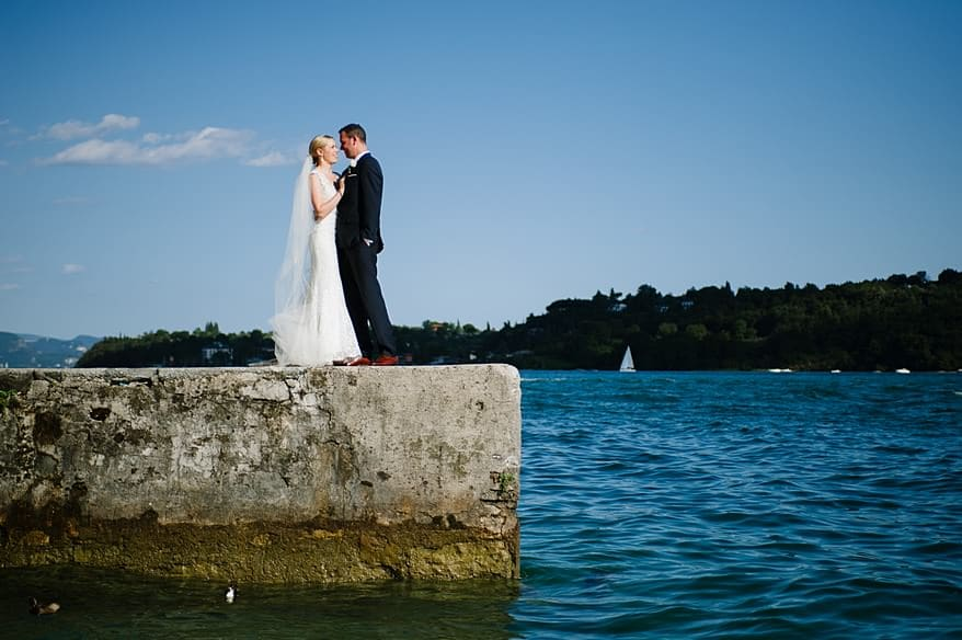 bride and grooms stood on the a pier at Lake Garda in Italy