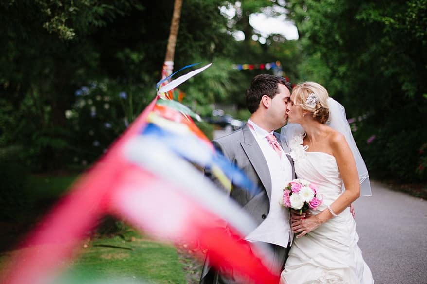 Bride and groom kissing near bunting at the Falmouth Hotel