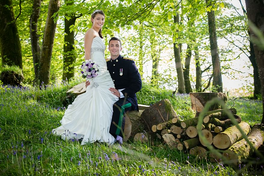 bride and groom sat on logs surrounded by blue bells at Trevenna Barns