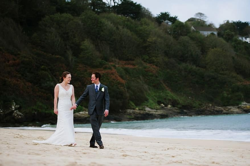 bride and groom walking on the beach at the Carbis bay hotel