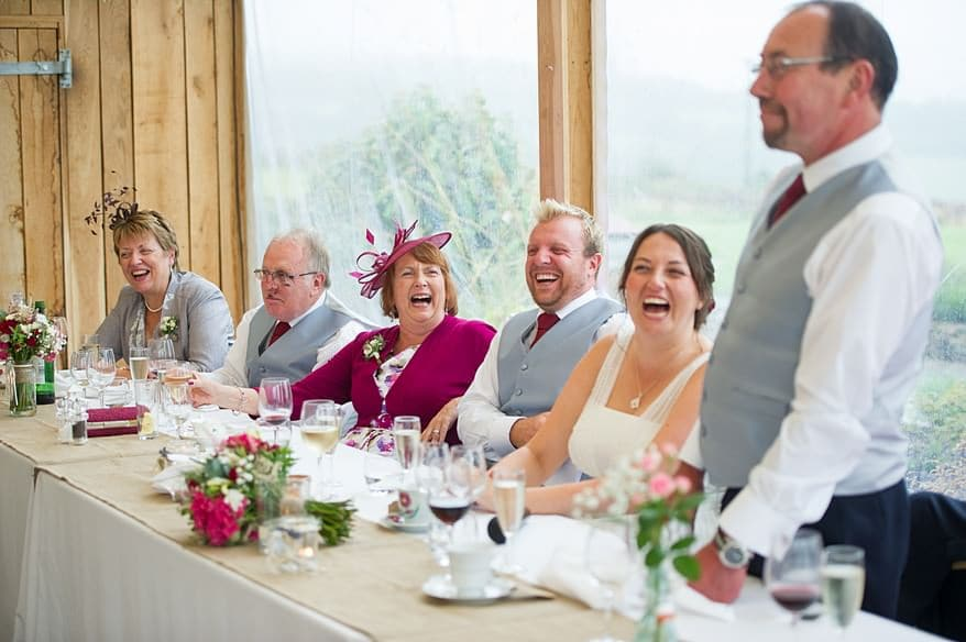 everybody laughing on the head table at a wedding in Trevenna barns