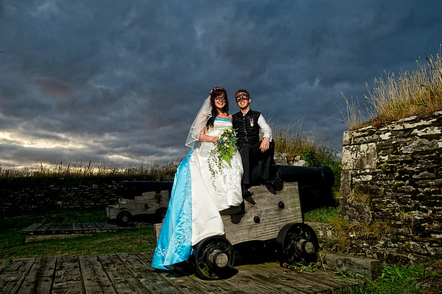 bride and groom sat on the canon at Pendennis castle