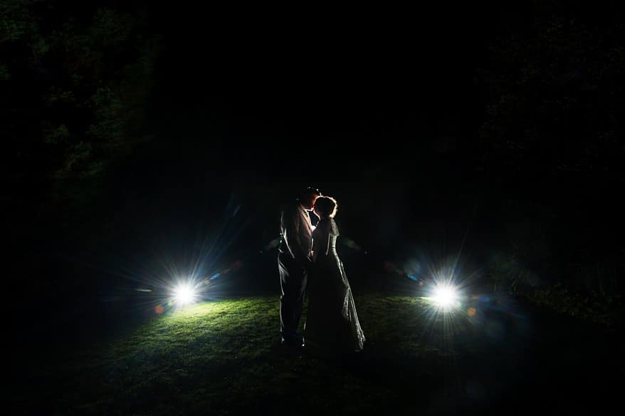 Bride and groom being lit by flash on the lawn of St Michaels hotel