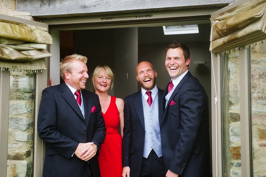 Grooms men and Groom laughing in the doorway at Trevenna Barns