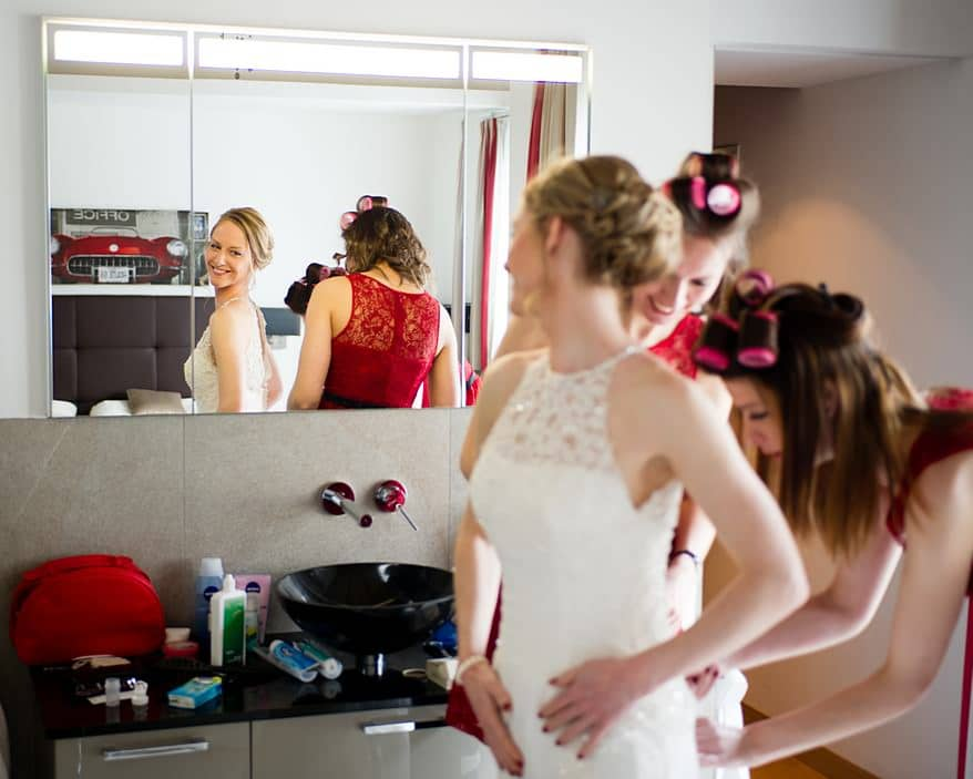 Bride smiling in the mirror while her bridesmaids tie the back fo the wedding dress in Zermatt