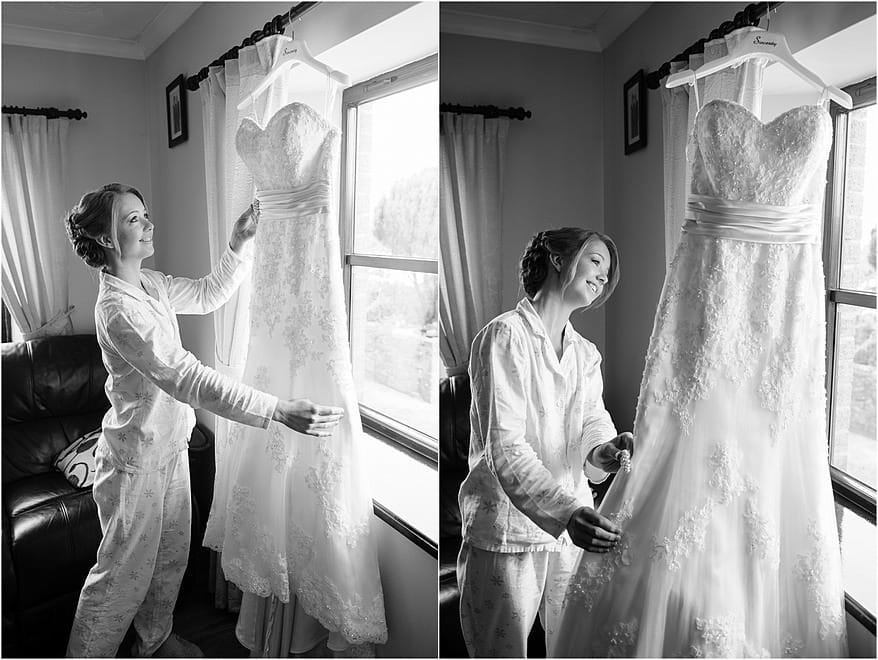 Bride loking at her dress hanging in the window
