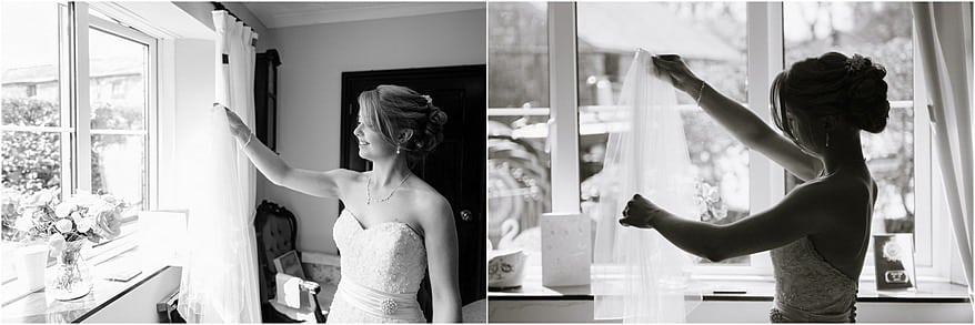 Black and white photograph of the bride about to put her veil in her hair