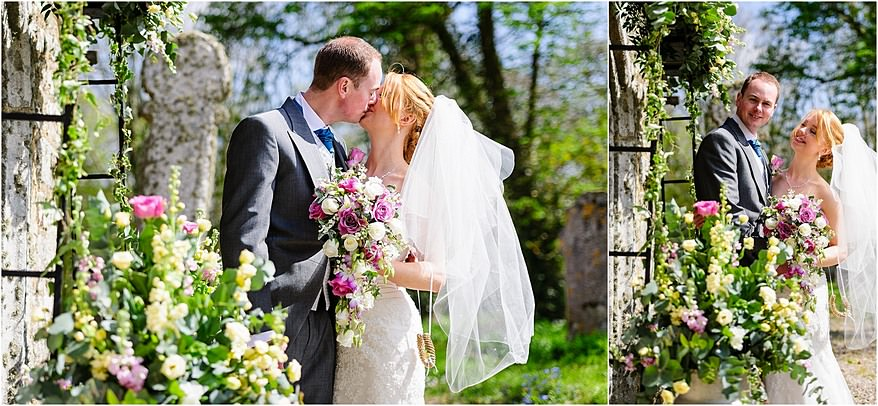Bride and groom kissing under the arch at St Allens church