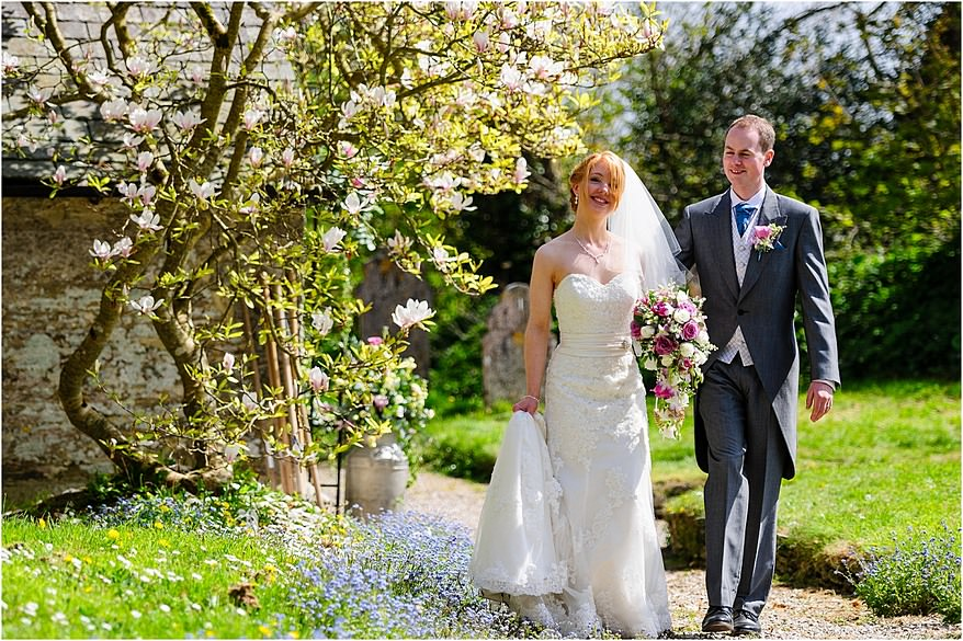 Bride and groom walking down path at the church at St Allen