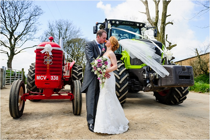 bride and groom kissing infront of their wedding tractors