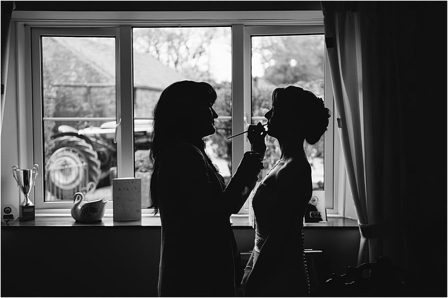 silhouette of the bride having her make up being applied