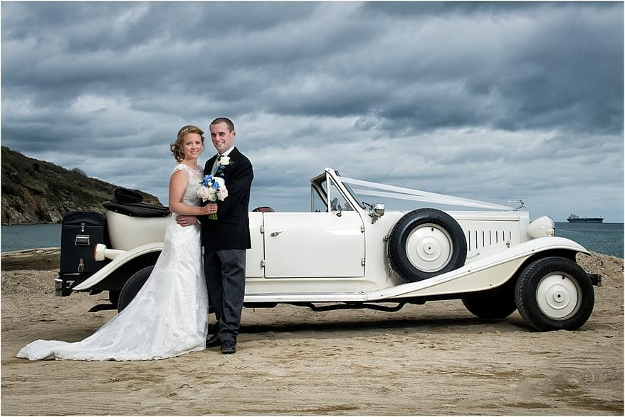 Bride and groom with a vintage Beauford at Maenporth Beach
