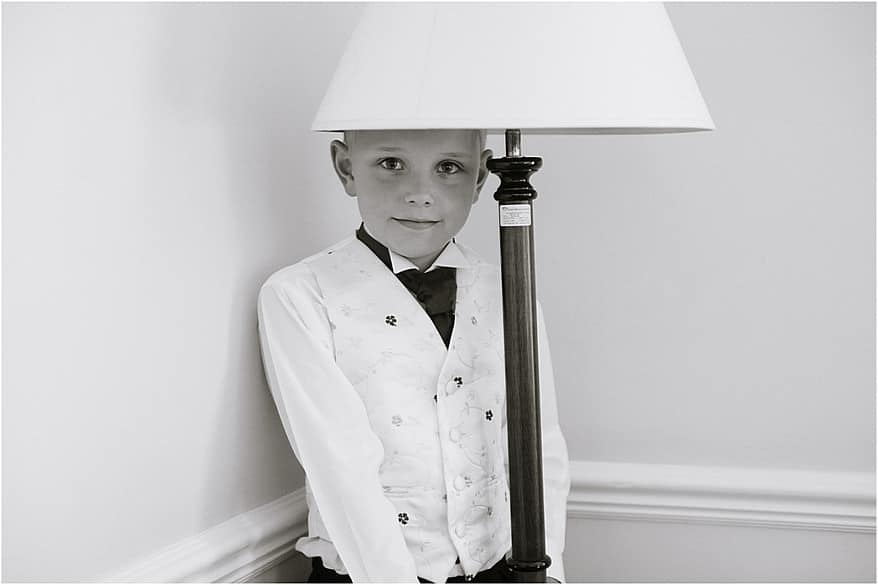 the paige boy hiding from the camera under a lamp shade