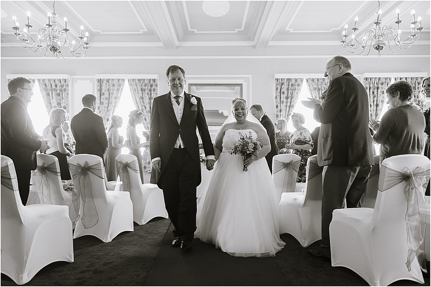 Bride and groom both walking down the isle after getting married at Tregenna Castle