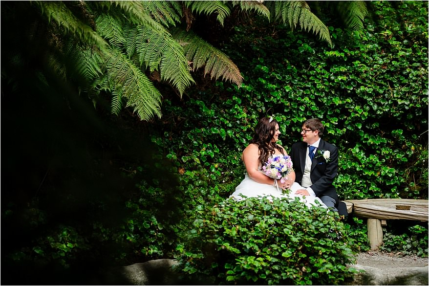 Bride and groom sat next to the pond at their Trebah Gardens wedding
