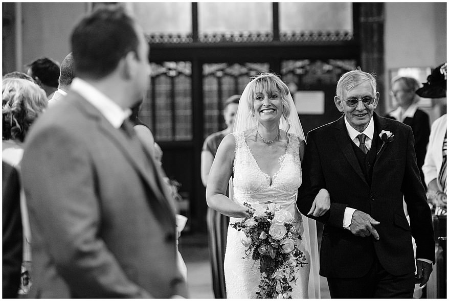 happy bride walking down the aisle at Saint Martin's church at Lewannick