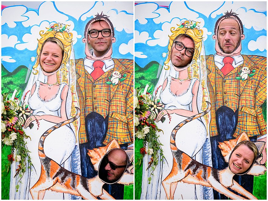 guest have their heads through a picture board at a village fete themed wedding