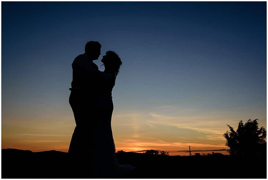 dramatic sunset at a coads green village hall wedding