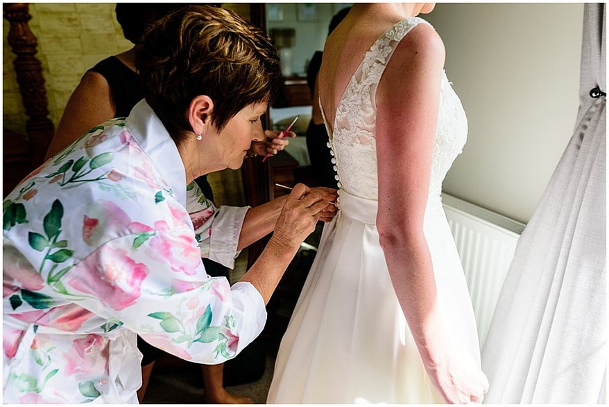 bride getting into her dress for her wedding at the alverton hotel 10