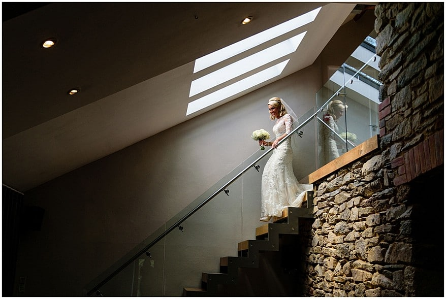 bride walking down the stairs at trevenna barns in bodmin 25