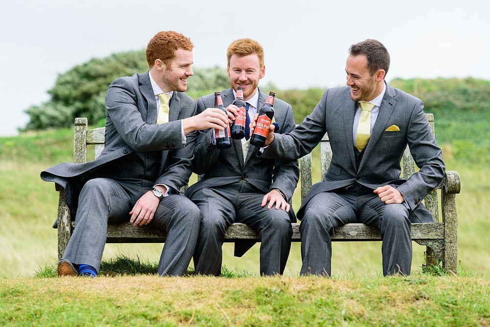 Grooms drinking beers for a wedding at St Enodoc's Church 27
