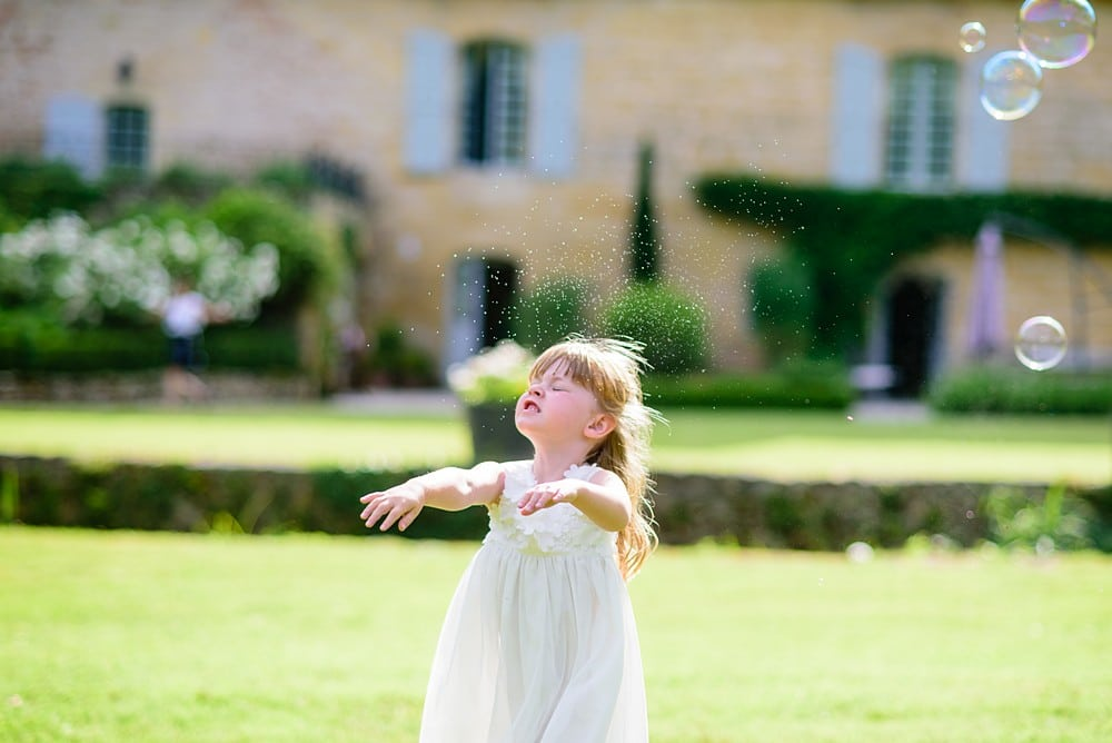 Flower girl playing with bubbles on the lawn at Chateau Forge Du Roy 78