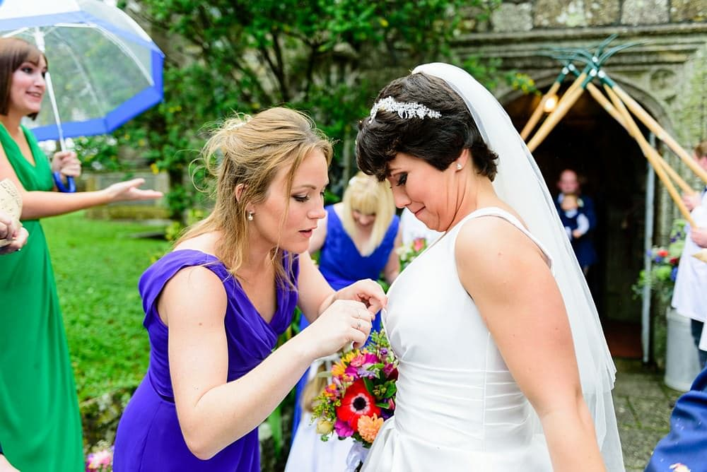 Bridesmaid picking confetti out of the brides cleavage