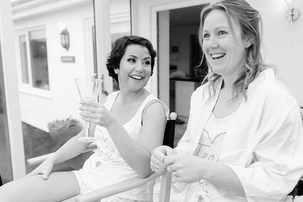 Bride enjoying a drink with her bridesmaid