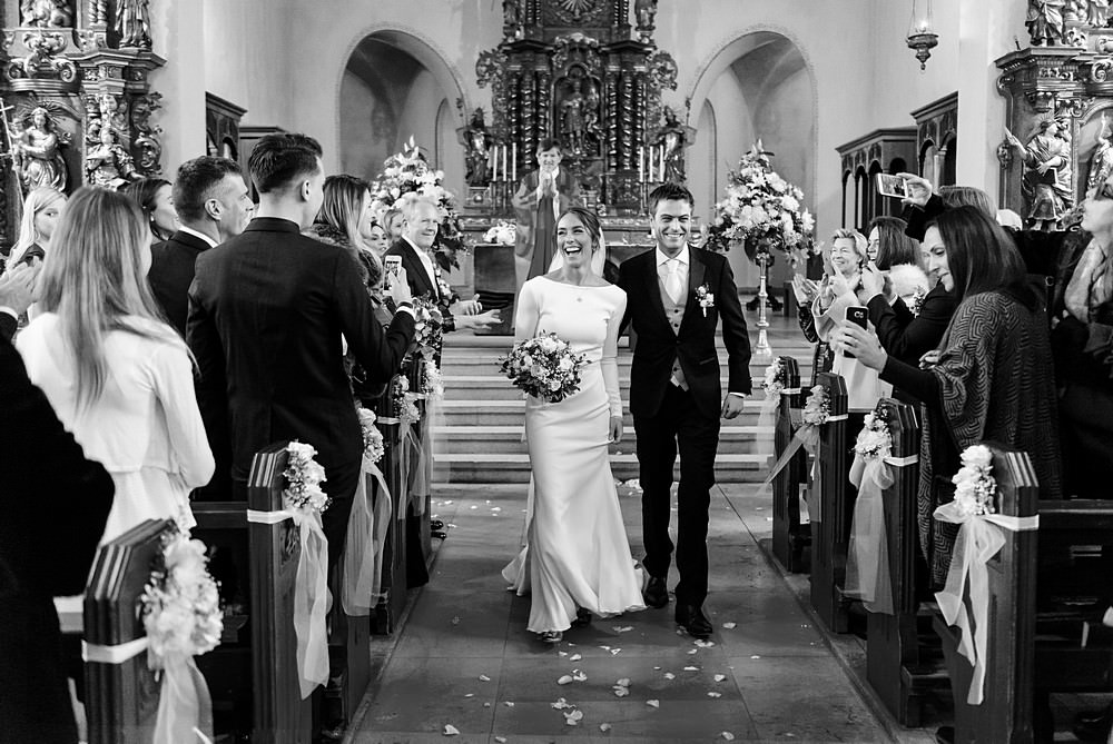 Bride walking down the aisle with her husband at St.Mauritius Church in Zermatt