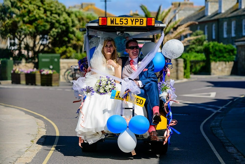 Bride and groom on a wedding golf cart on the Isles of Scillies
