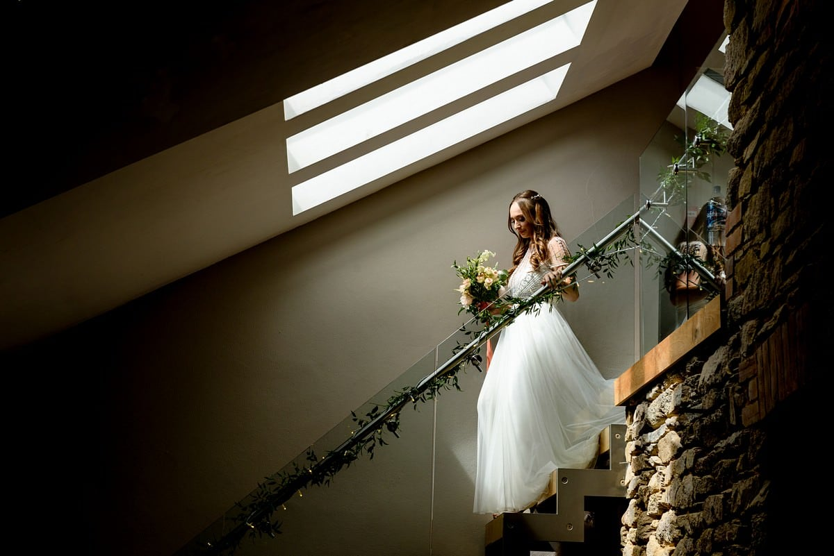 Bride walking down the stairs at Trevenna barns